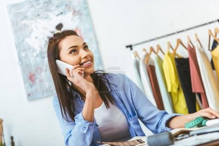 attractive designer talking by smartphone at working place