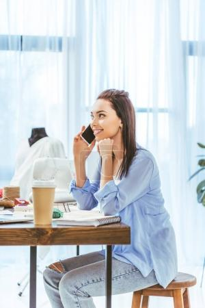 beautiful designer talking by smartphone at working place