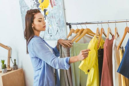 Photo for Beautiful designer looking at shirts on hangers - Royalty Free Image
