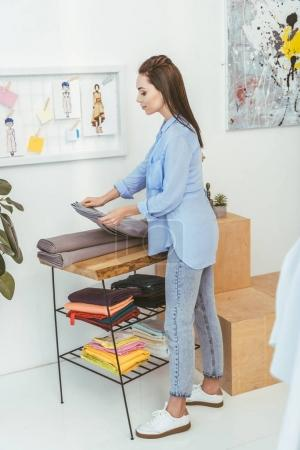 beautiful seamstress taking gray fabric from stack
