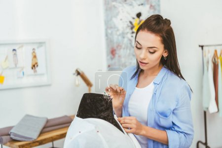young beautiful designer putting pin into fabric on mannequin