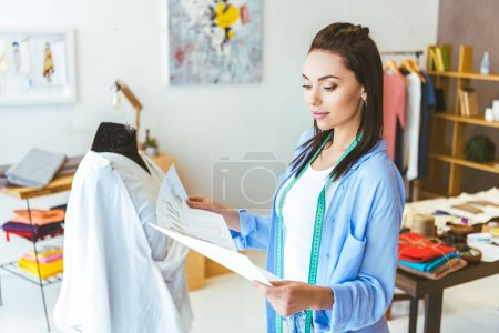 designer looking at sketches of white dress