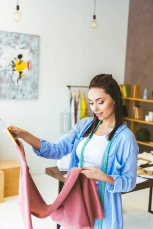 tailor looking at pink dress in working room