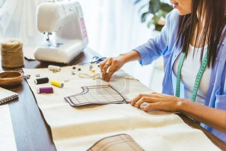 cropped image of smiling seamstress measuring pattern at table