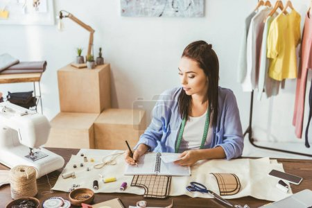 seamstress writing down notes to notebook
