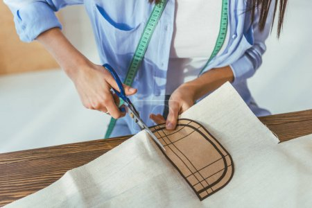 cropped image of seamstress cutting fabric with scissors