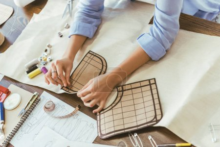 cropped image of seamstress putting pin into pattern and fabric