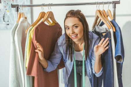 Photo for Smiling seamstress looking out from clothes on hangers - Royalty Free Image