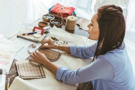 seamstress measuring pattern at working table