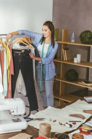 seamstress holding trousers on hanger at her working place