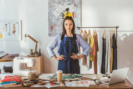 seamstress standing at working place and looking at camera