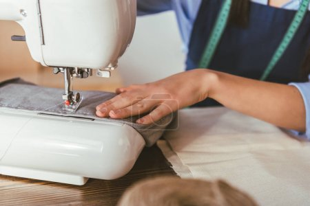 cropped image of seamstress sewing with sewing machine