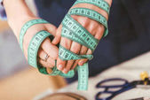 cropped image of seamstress hands winded up with tape measure
