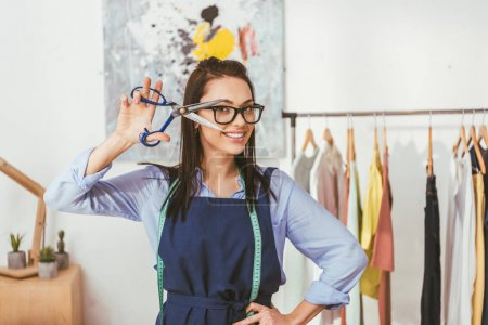 smiling seamstress posing with scissors at working place