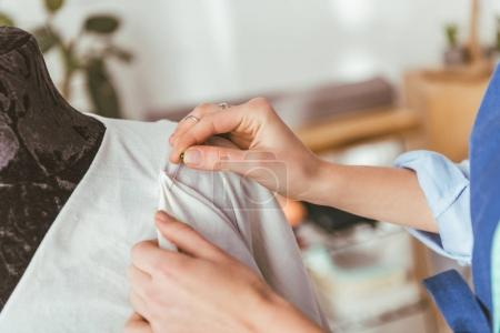 cropped image of tailor putting pin into white dress on mannequin