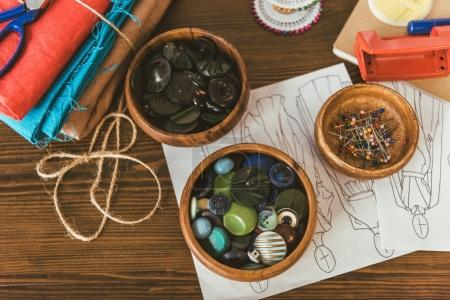 wooden bowls with buttons and pins on table