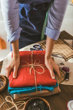 cropped image of seamstress taking stack of colored fabric