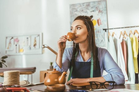 attractive seamstress sitting at table and drinking tea