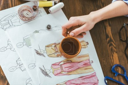 cropped image of seamstress holding cup of tea above sketches