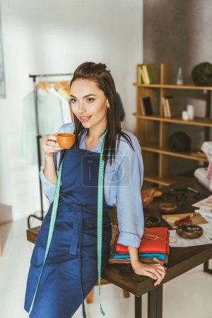 attractive seamstress leaning on table, holding cup of tea and looking away