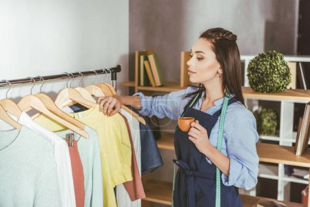 seamstress looking at clothes on hangers and holding cup of tea
