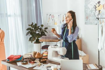 happy seamstress talking by smartphone in working room and holding cup of tea