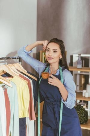 happy seamstress leaning on rack with clothes on hangers