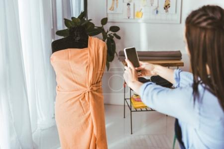 seamstress taking photo of dress on mannequin with smartphone