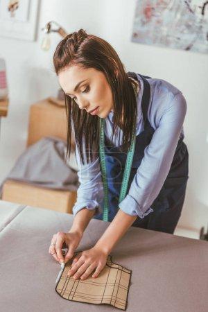 beautiful seamstress making pattern with piece of chalk on fabric