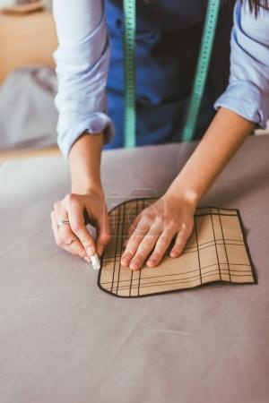 cropped image of beautiful seamstress making pattern with piece of chalk on fabric