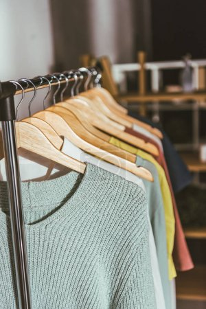 row of different colored sweaters and shirts on hangers