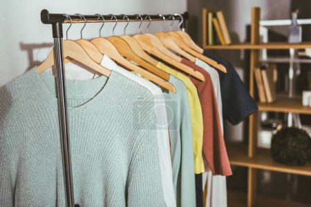 Photo for Different colored sweaters and shirts on hangers - Royalty Free Image