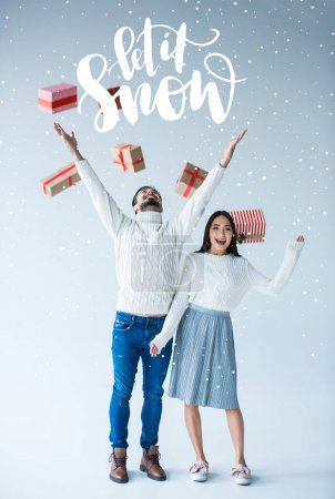 "Photo for Multicultural couple with falling wrapped christmas presents, isolated on grey with ""Let it snow"" lettering - Royalty Free Image"