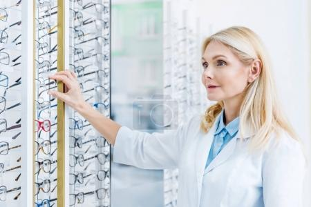 professional ophthalmologist standing in optics with glasses on shelves