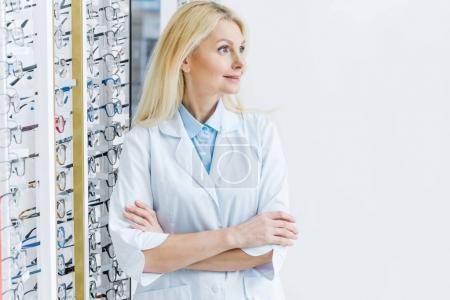 Photo pour Ophtalmologiste féminine debout dans l'optique avec des lunettes sur les étagères - image libre de droit