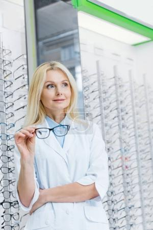 beautiful female ophthalmologist holding glasses and standing in optics