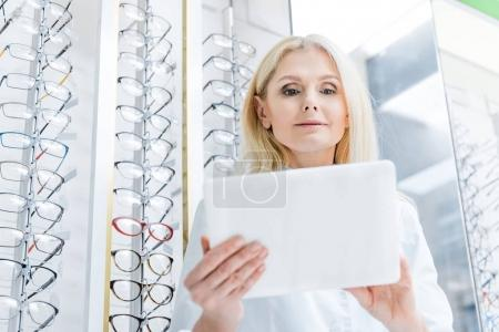 professional female ophthalmologist working with digital tablet in optics with glasses on shelves