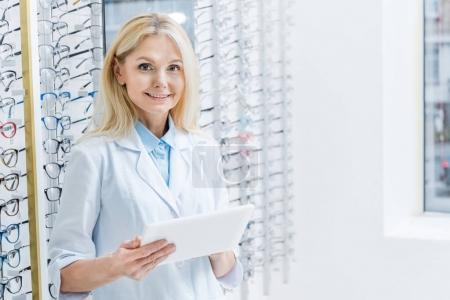 professional female ophthalmologist working with tablet in optics with glasses on shelves