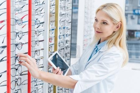 professional female ophthalmologist using digital tablet in optics with glasses on shelves