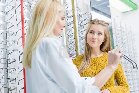 optician helping client to choose eyeglasses in optics