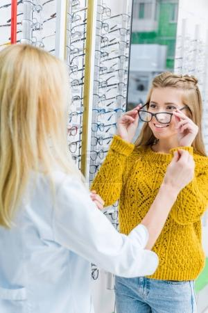optometrist helping client to choose eyeglasses in optics