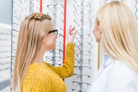 oculist helping client to choose glasses in optics
