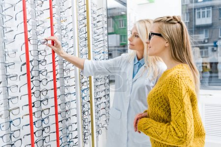 optician helping client to choose glasses in optics