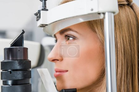 close up of attractive patient examining her eyes with slit lamp in clinic