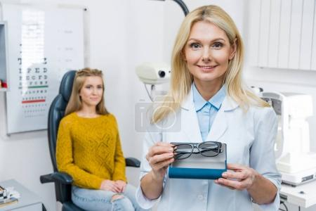 optician in white coat holding eyeglasses while patient sitting behind