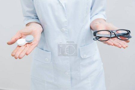 Foto de Vista recortada de optometrista en bata blanca con anteojos y lentes de contacto, aislado en blanco - Imagen libre de derechos