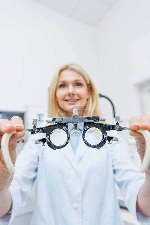optician in white coat holding trial frame in clinic