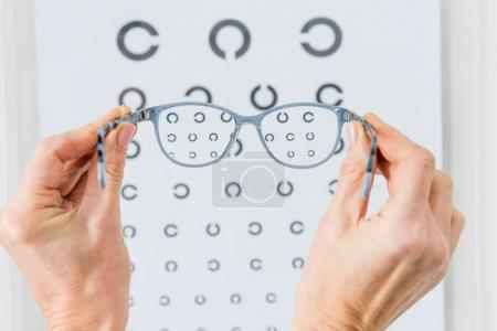Photo for Cropped view of person holding glasses with eye chart behind - Royalty Free Image