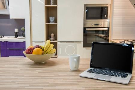 Photo pour Intérieur confortable cuisine moderne avec ordinateur portable et les fruits dans un bol - image libre de droit
