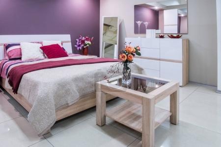 уютный современный интерьер спальни в фиолетовых тонах